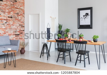 Black chairs at dining table and poster in flat interior with grey sofa against red brick wall. Real photo #1205887804