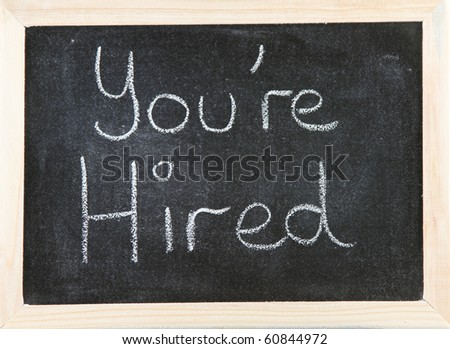 Black chalk board with wooden framed surround with the words You're Hired.