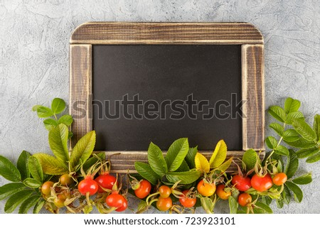 Black chalkboard and dogrose berry, Autumn decorations. Top view, space for text on the board