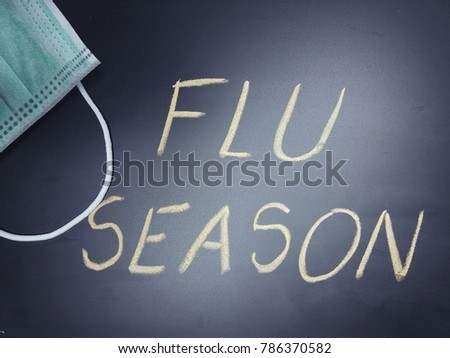 Black chalkboard with phrase Flu season written on it and a face mask, flu season or influenza concept #786370582