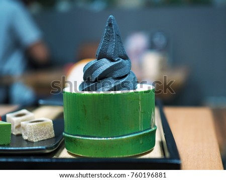 Black charcoal soft serve ice cream, served in green bamboo shape cup, Traditional Japanese confectionery, Healthy concept. Selective focus. #760196881