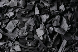 Black charcoal texture background. Close-up