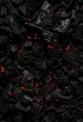Black charcoal with red streaks of heat. Black textured background.