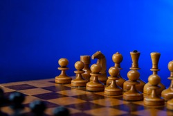 Black chess pieces against white chess pieces on a chessboard on a blue background with place for text. Old vintage chess