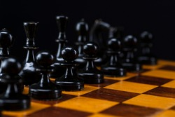 Black chess pieces on a chessboard. An army of black pawns on the table. Old vintage chess