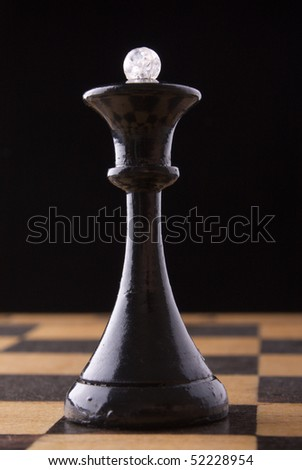 black chess queen stands on a chessboard, black background
