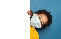 Black child boy in medical protective face mask holding white empty paper singbard