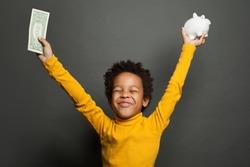 Black child boy with american dollars money having fun on black