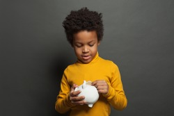 Black child putting in money bank coin