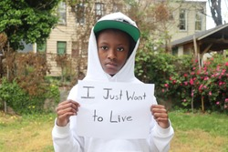 Black child wearing hat and hoodie holding sign with words I Just Want To Live written on it standing outdoors