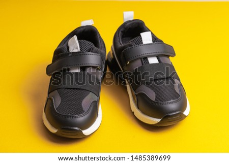 Black children's school sneakers on a flypaper on a yellow background #1485389699