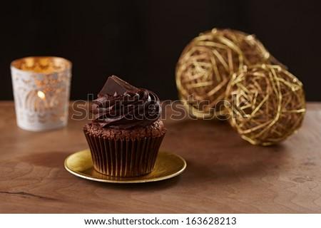 Black chocolate cupcake on black Christmas background