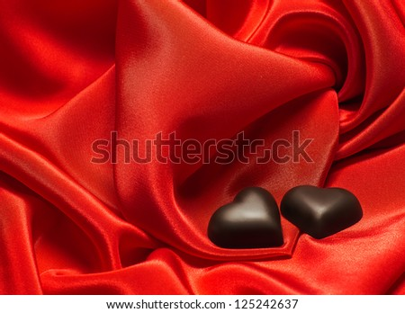 Black chocolate hearts on red silk