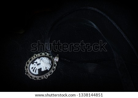 Black choker with skeleton cameo pendant on a dark background close up #1338144851