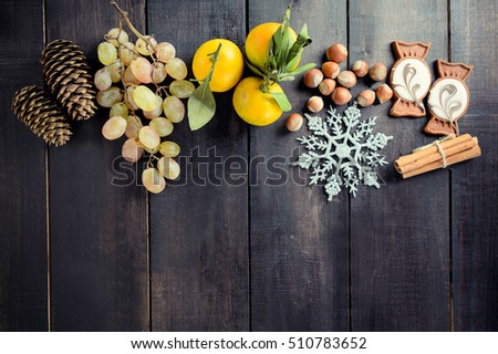 Black Christmas Background with empty copy space. Grapes, tangerine and nuts as a decorative xmas frame for xmas concept or cards #510783652