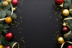 Black Christmas background with festive decorations, baubles, fir tree branches, confetti. Christmas holiday celebration, winter, New Year concept. Christmas banner mockup, greeting card template.