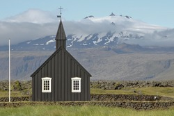 Black church in Iceland in front of a glacier