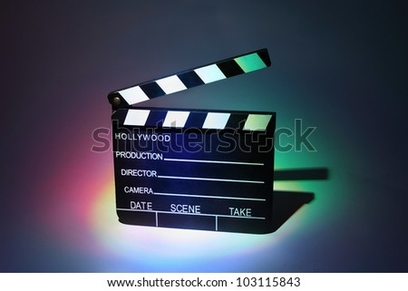 Black cinema clapperboard, which is multicolored highlighted - stock photo