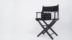 Black Clapper board or movie slate with director chair use in video production or movie and cinema industry. It's put on white background. .