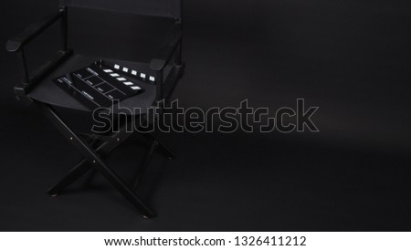 Black Clapperboard or clap board or movie slate with director chair use in video production ,film, cinema industry on black background. #1326411212