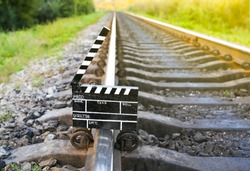 Black clapperboard with train tracks on background. Directing and filming cinema movie. Travel story.