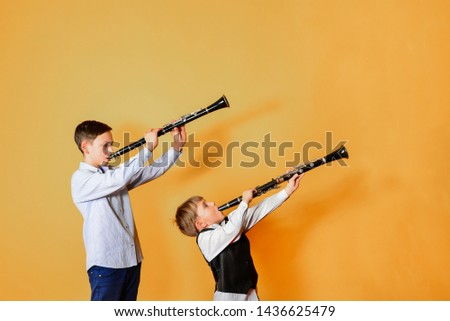 Black clarinet on an orange background in the hands of young performers of the folk mazy. Two brothers with clarinets, performing at a musical concert. #1436625479