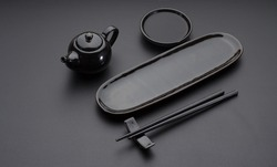 Black clear set of dishes for sushi and rolls. Japanese chopsticks, plate, saucer on the black table.