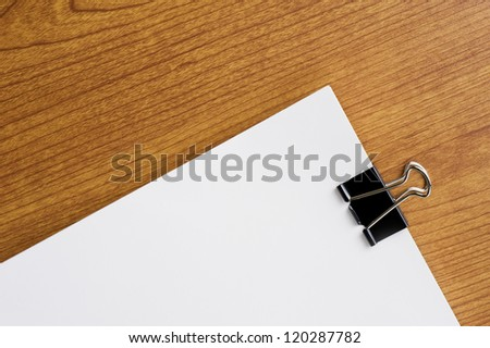 Black clip and blank paper on wooden desk