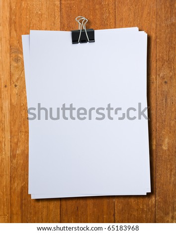 Black clip and White blank note paper hang on wood pane