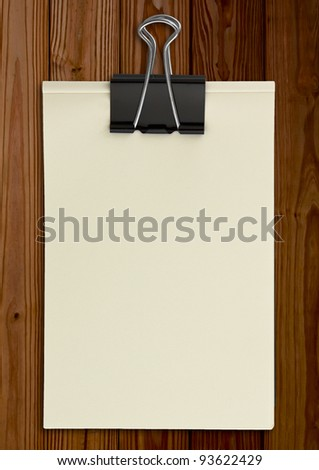 Black clip and White blank note paper  on wood panel