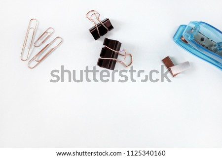 Black clips, clamps, blue stapler and staples  as a method of use with white background. Office clips. Stationery. Methods of binding documents. Business background.  Office flat lay  accessories.