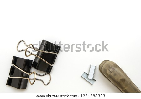 Black clips, clamps, brown stapler and staples as a method of use with white background. Office clips. Stationery. Methods of binding documents. Business background. Office flat lay accessories