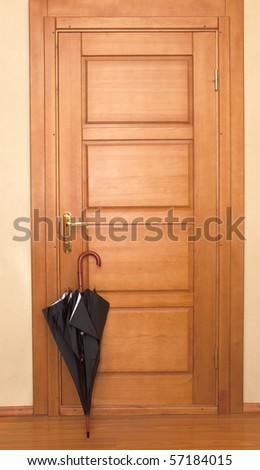 black closed umbrella at wooden entrance door