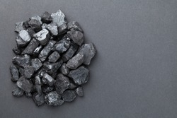 Black coal pile over graphite background. Copy space. Top view