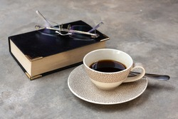 Black coffee and book with glasses