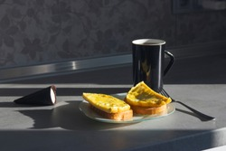 black coffee cup with black dessert cone and omelet on a white plate on a gray kitchen table with hard sun shades