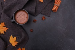 Black coffee cup, yellow maple leaves, spices, grey scarf on dark grey background. Copy space, top view. Autumn background, fall season, thanksgiving, coffee shop menu concept.