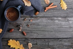 Black coffee cup, yellow oak leaves, acorns, cinnamon, grey scarf on rough old wooden boards. Copy space, top view. Autumn background, fall season, thanksgiving, coffee shop menu, hot drink concept