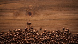 Black coffee grains lie on a brown wooden table, background image