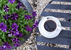 black coffee in a coffee cup top view with purple Petunia flowers at Muak Lek, Saraburi
