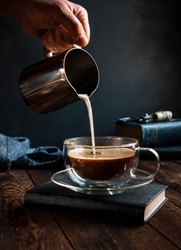 Black coffee in a cup, jug with milk in your hand. Dark wooden table, in the background books.