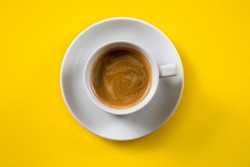 Black coffee in a cup on a yellow background
