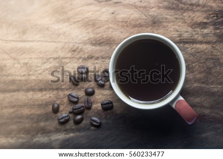 Black Coffee in a white cup and coffee been on the brownish gray wooden table #560233477