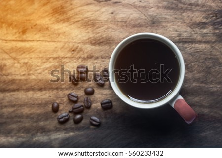Black Coffee in a white cup and coffee been on the wooden table #560233432