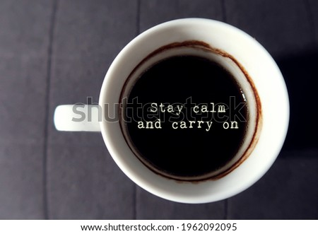 Black coffee in a white cup with text STAY CALM AND CARRY ON , morning self reminder to set peace of mind, let go all stress and anxiety , aiming to goal with inner strength and self confidence ストックフォト ©