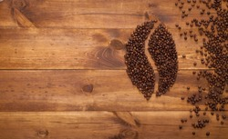 Black coffee in bean seed shape and scattered on brown wooden table, dark cofee espresso roasted grain flavour aroma cafe, natural coffe shop background, top close up view from above, copy space