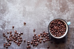 Black coffee in Blue cup on freshly roasted coffee beans background. Top view.