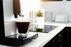 Black coffee in glass from coffee maker machine. coffee machine lungo kitchen glass hot italian concept