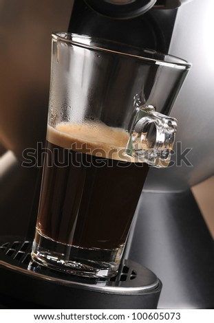 Black coffee in the glass and coffee machine