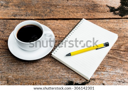 Black coffee in white cup with note book and yellow pen on wood background.